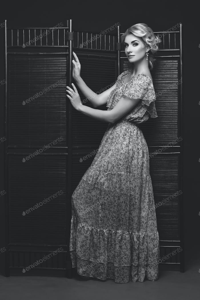 Beautiful girl standing near folding screen