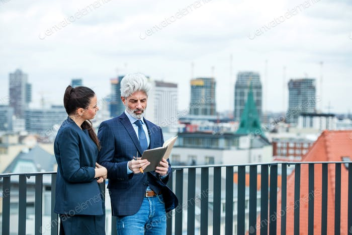 A businessman and businesswoman with diary standing on a terrace, working.