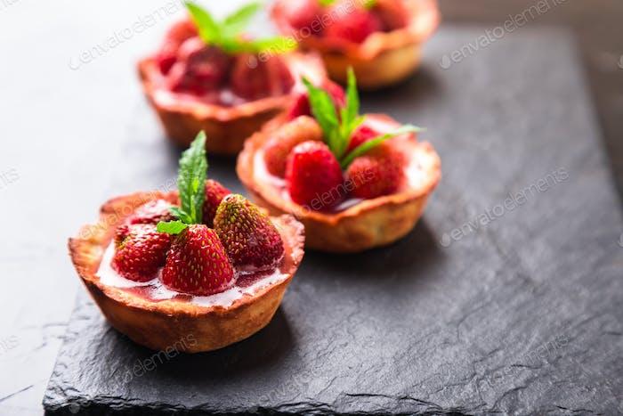 Homemade strawberries tarts on slate plate, black background
