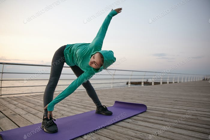 Porträt einer wunderschönen jungen Frau, die Yoga praktiziert, gekleidete Sportkleidung
