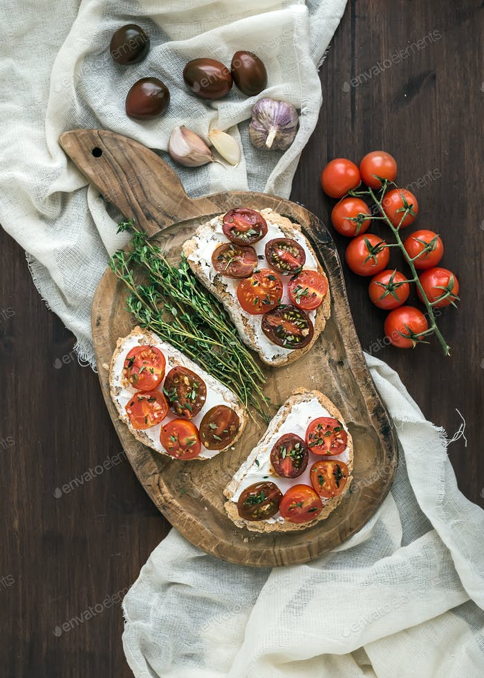 Sandwiches brushtta with roasted cherry tomatoes, soft cheese