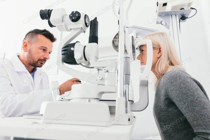 Optician checking woman's eyes with special equipment.