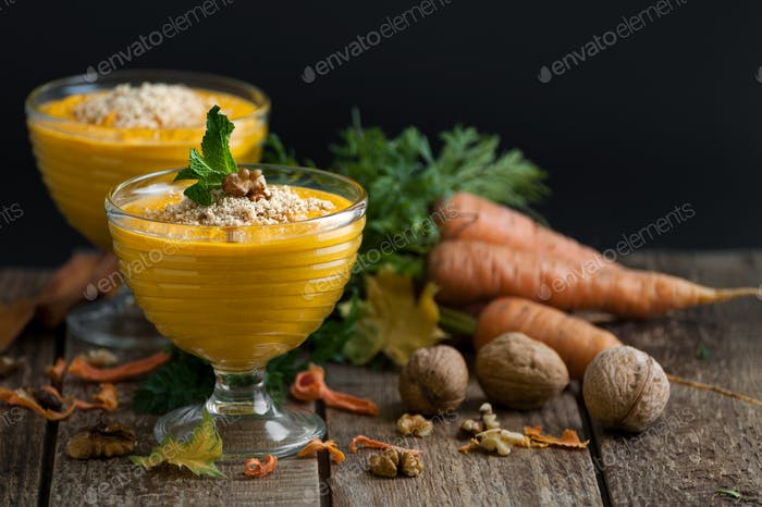 Carrot pudding with crushed walnut on a black background.