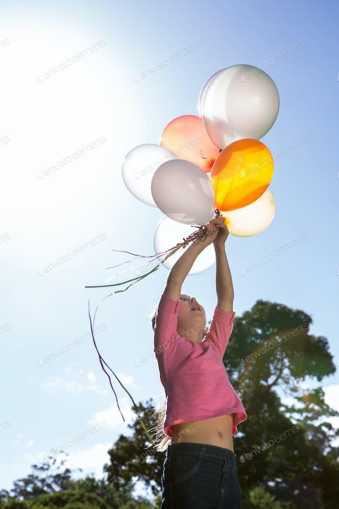 Glückliches kleines Mädchen halten Ballons an einem sonnigen Tag