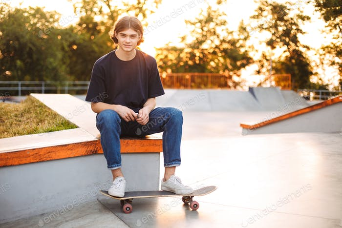 Young skater in black T-shirt and jeans joyfully looking in came