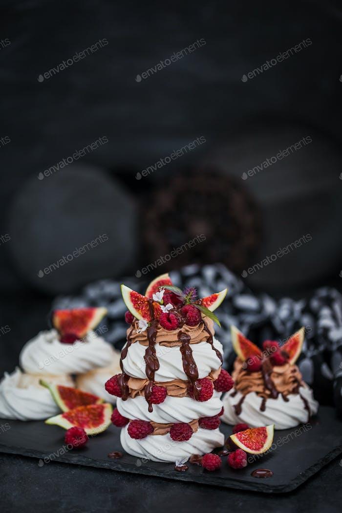 Delicious Pavlova meringue cakes decorated with chocolate cream,