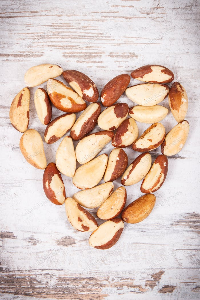 Heap of brazil nuts in shape of heart, healthy food containing natural minerals
