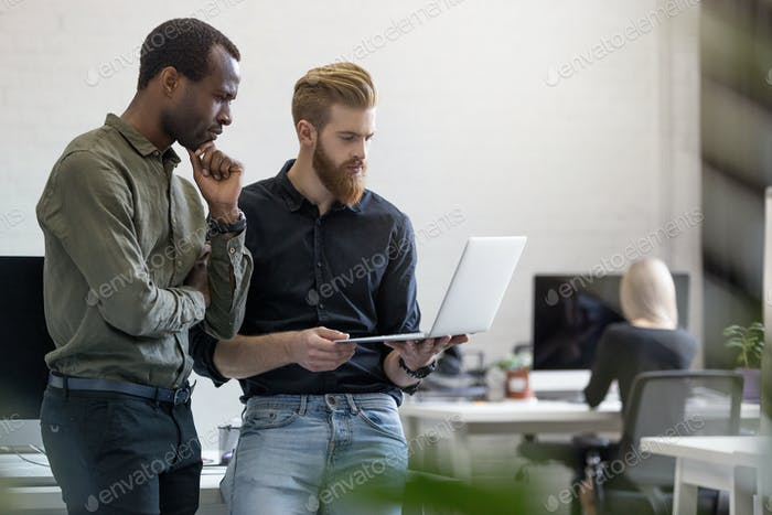Two worried young business men looking at the laptop