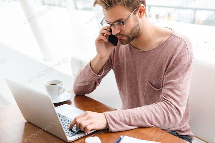 Bild des Menschen, der auf dem Handy spricht und am Laptop im Café drinnen arbeitet