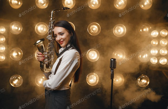 Female saxophonist poses with saxophone on stage