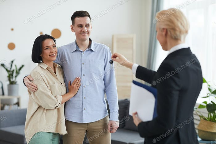 Realtor giving the keys to young couple