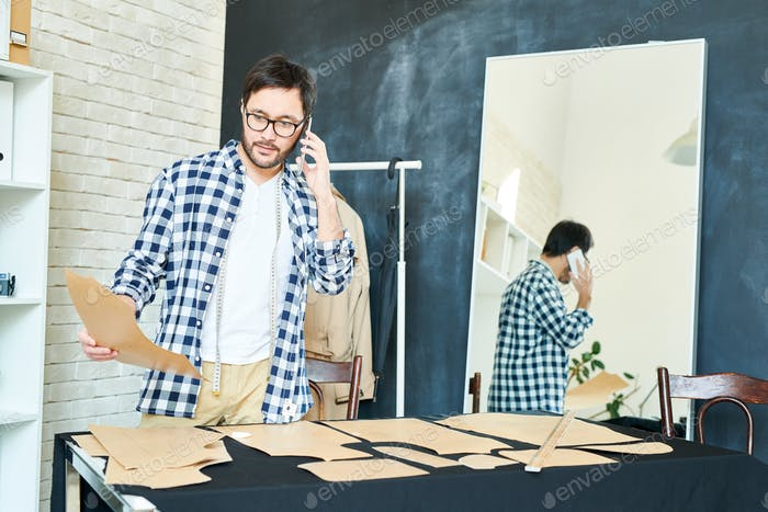 Working tailor in atelier having call