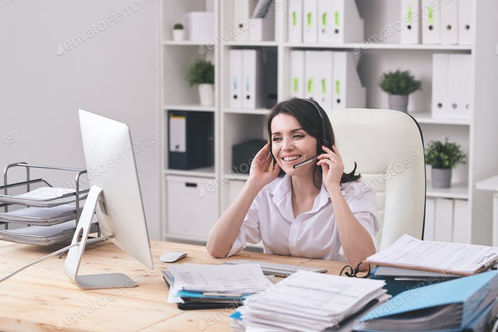 Happy young customer support representative with headset looking at client