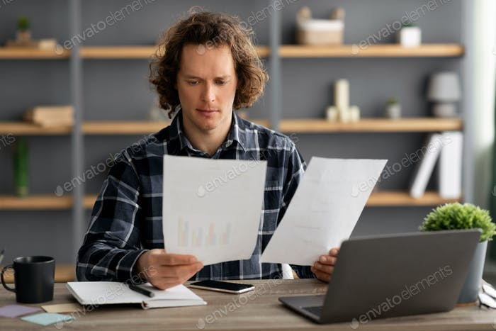 Businessman Reading Business Reports And Financial Bills Sitting At Workplace