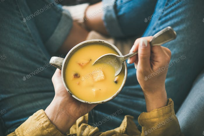Female sitting keeping mug of Fall warming pumpkin cream soup