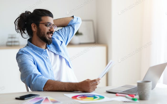 Western designer man working with colour swatches at desk in home office