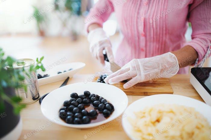 Unerkennbare Frau mit Handschuhen Kochen in der Küche drinnen. Hygiene-Konzept