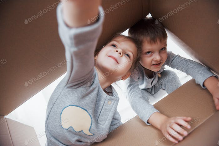 Two a little kids boy and girl opening a cardboard box and climbing in the middle of it
