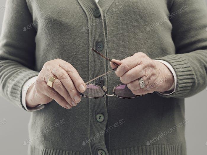 Senior Dame Hände halten Brille