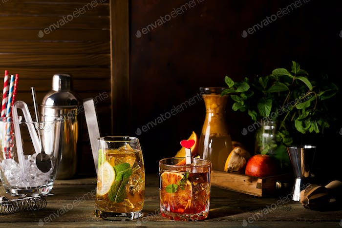 Different alcoholic drink in glass with fruits on dark wooden background