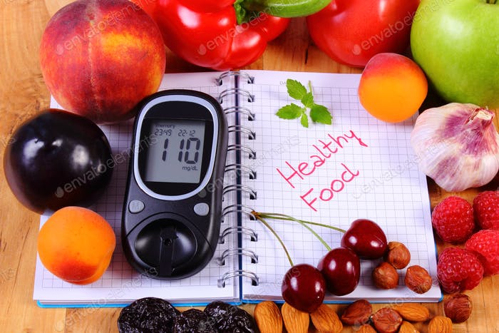 Fruits and vegetables, glucometer for checking sugar level and notebook for notes