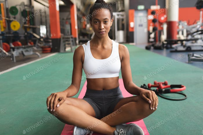 African-American woman sitting crosslegged on a yoga mat inside the a room at a sports center