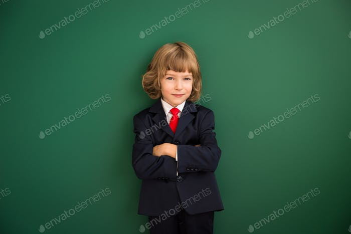 Kid with drawn robot hands against blackboard