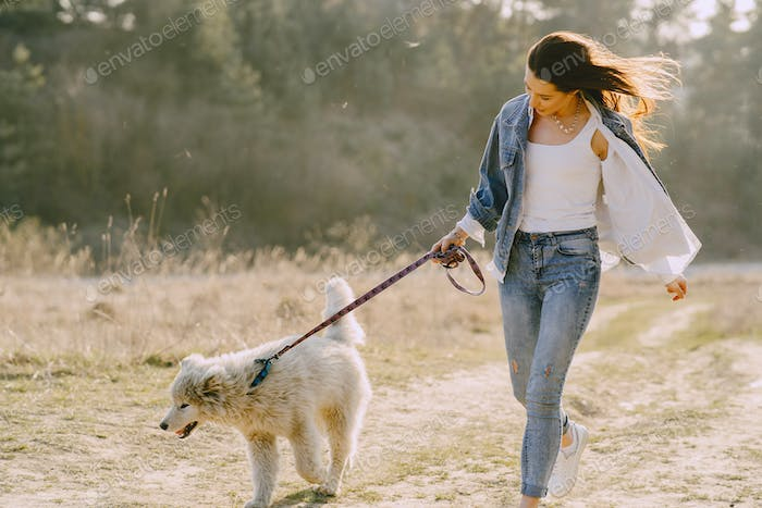 Stylish girl in a spring field with a dog