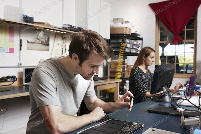 Un joven y una mujer trabajando en un banco en un laboratorio de tecnología.