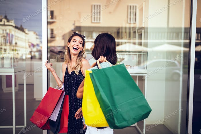 Shopping, sale, happy friends and tourism concept. Beautiful girls with shopping bags in ctiy