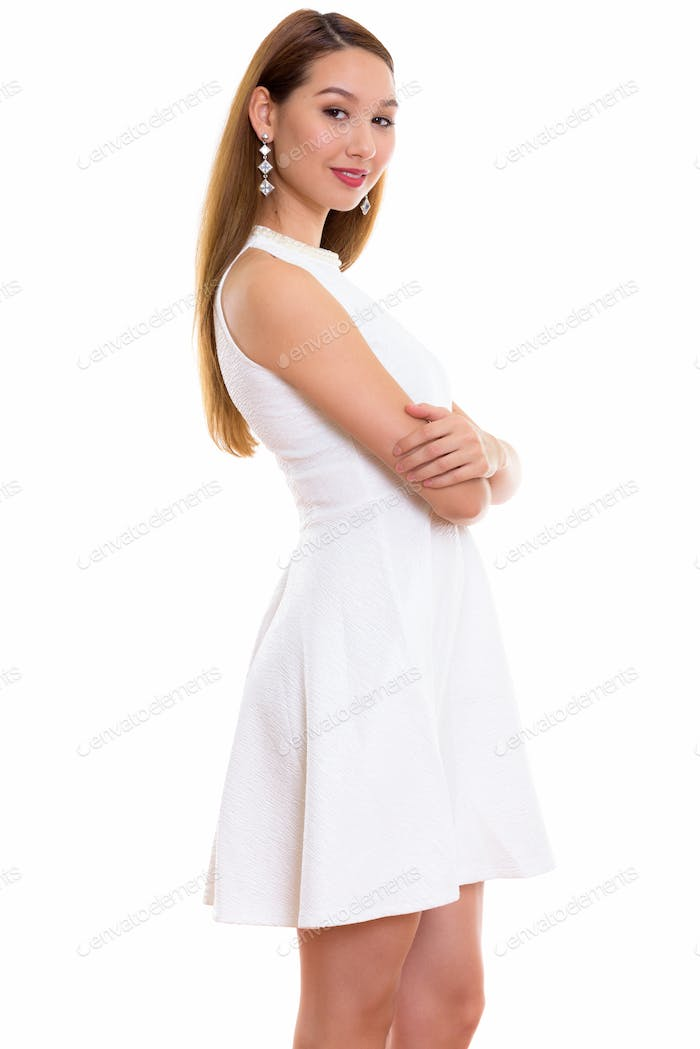 Studio shot of young beautiful Asian woman standing with arms cr