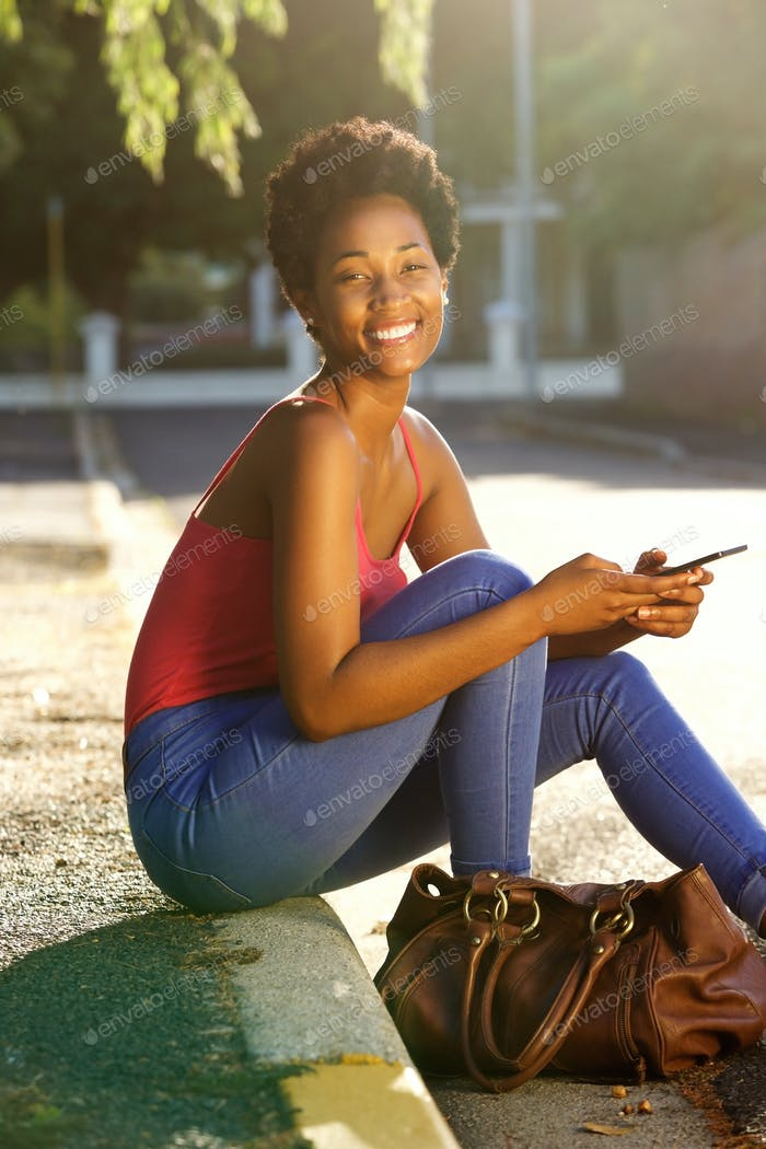 Happy young woman sitting along a street with a mobile phone