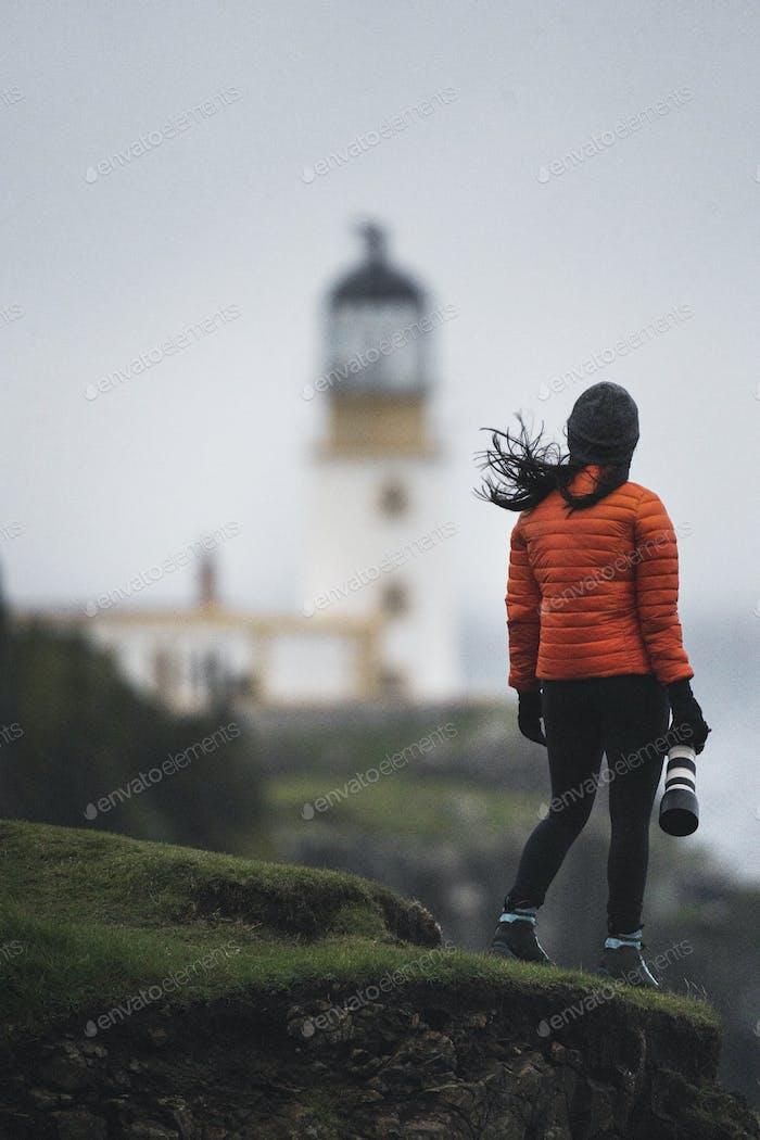 Female photographer at Neist Point Lighthouse, Isle of Skye, Scotland