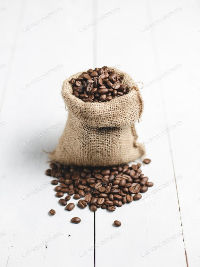 coffee beans in wooden bag with white wood background