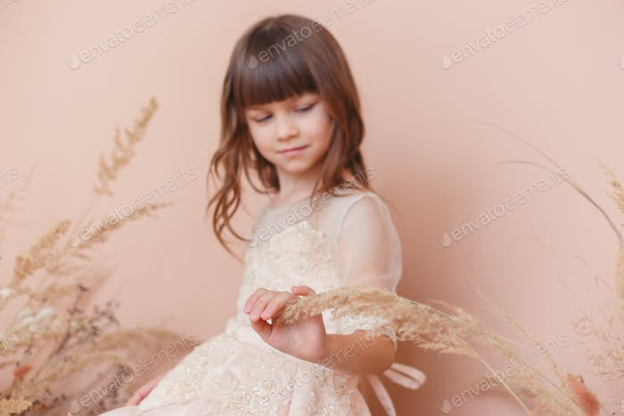 Young model girl in beige dress posing on pastel color background