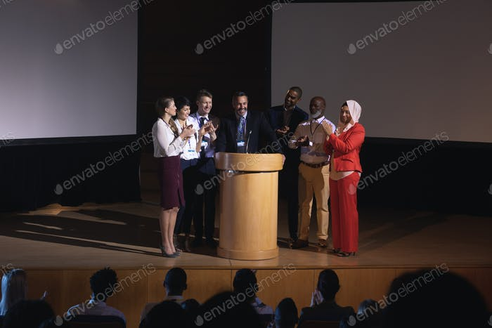 Business colleagues clapping hand for there colleague  for the success in the auditorium