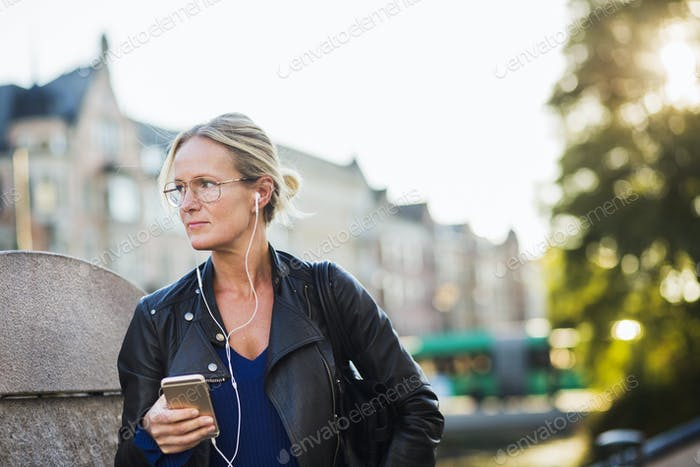 Mature woman listening to music through earphone while standing at street
