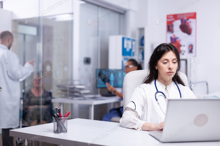 Young medic typing on laptop sittting in private clinic