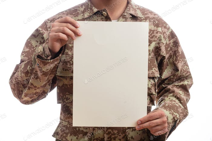 Young soldier holding a blank paper standing on white background