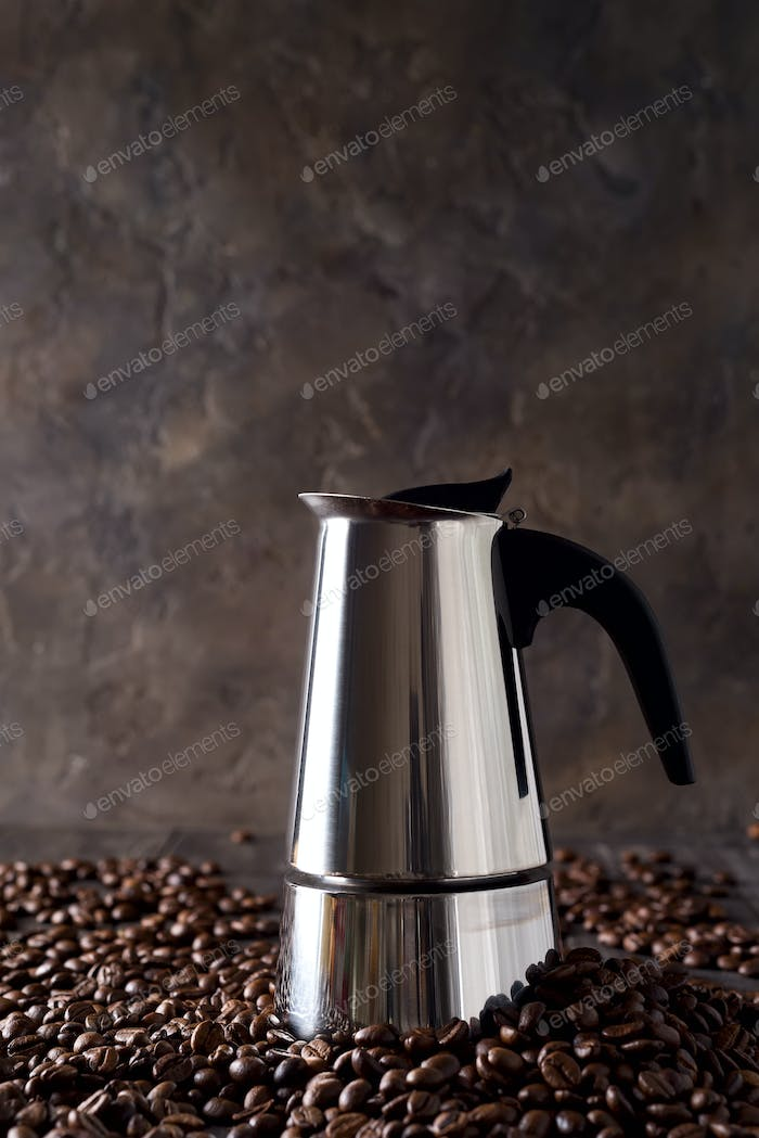 geyser coffee maker on the background of coffee grains on a dark wooden background, copy space
