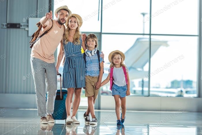 smiling family walking on boarding together in airport
