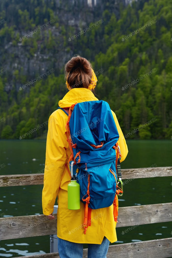People, recreation and nature concept. Back view of female traveler with big tourist backpack, wears
