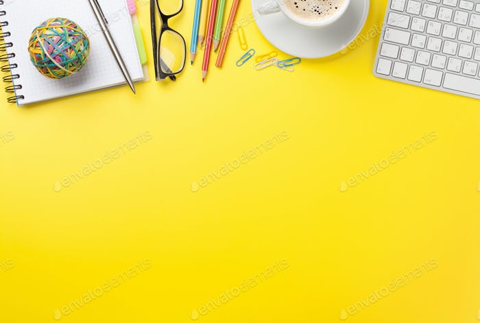 Office yellow backdrop with coffee, supplies and computer