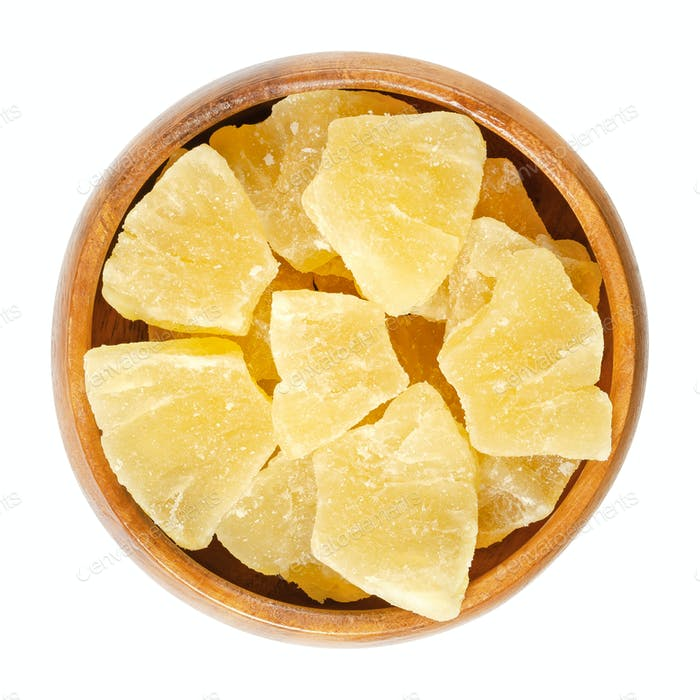 Candied pineapple pieces in wooden bowl over white