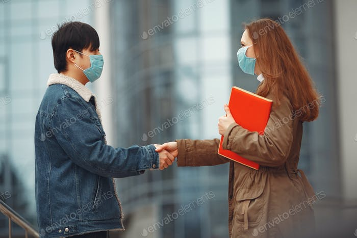 Chinese man and a woman in disposable masks are shaking hands