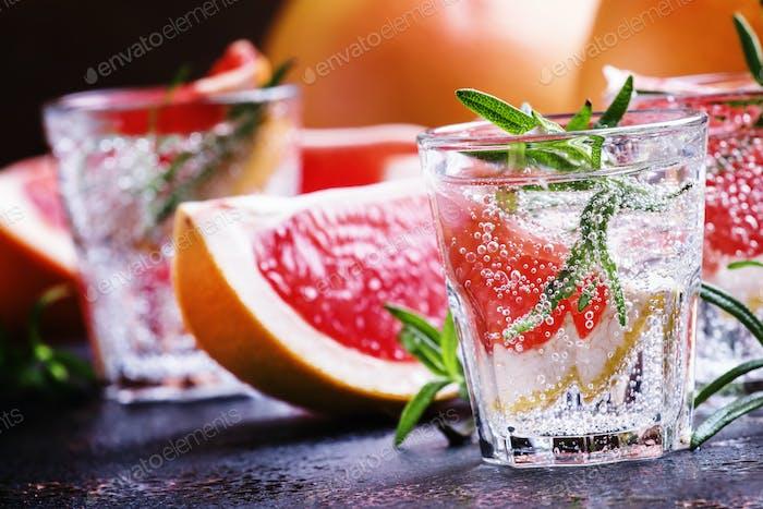 Alkoholischer Cocktail mit Grapefruit, Soda, Eis, Gin und Rosmarin
