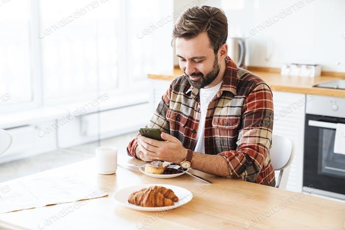 Retrato de hombre alegre usando celular mientras desayunan