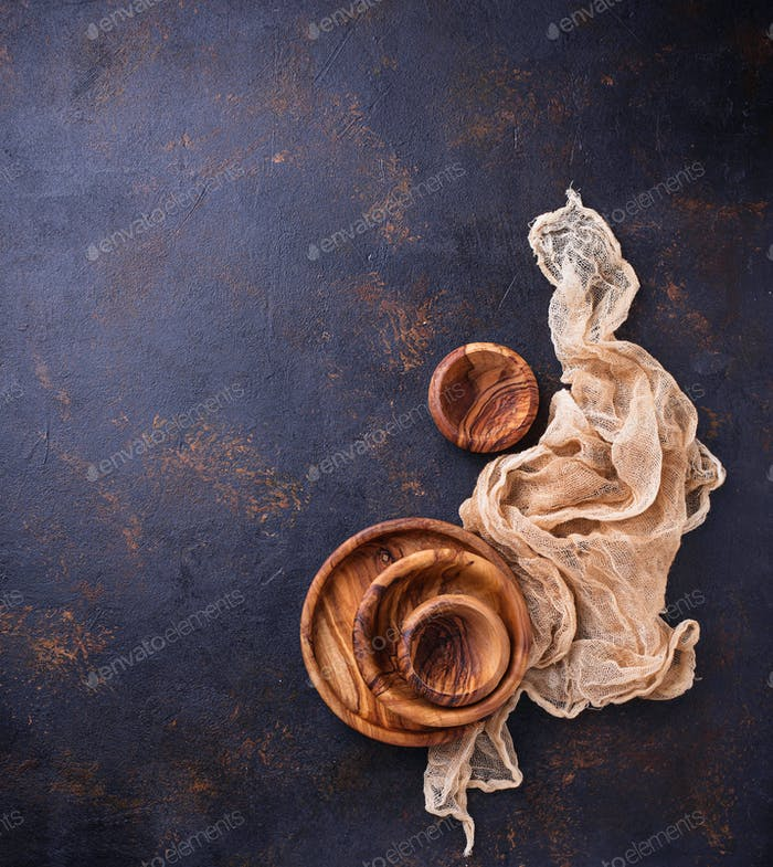 Empty wooden plate and bowls on rusty background