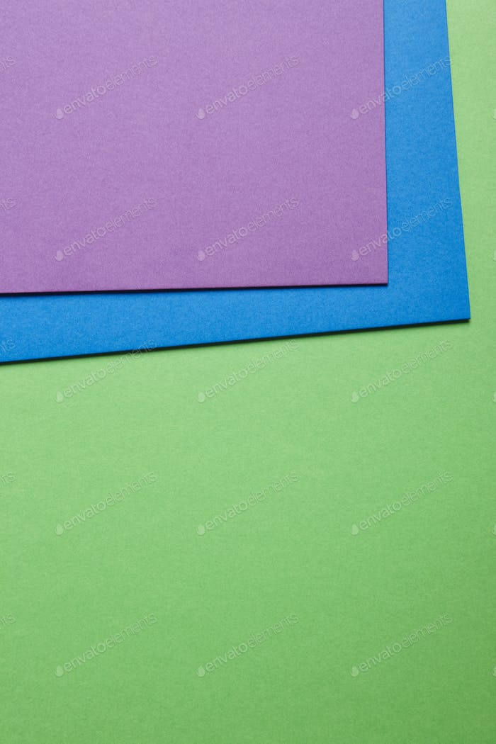 Colored cardboards background in green blue purple tone. Copy space. Horizontal