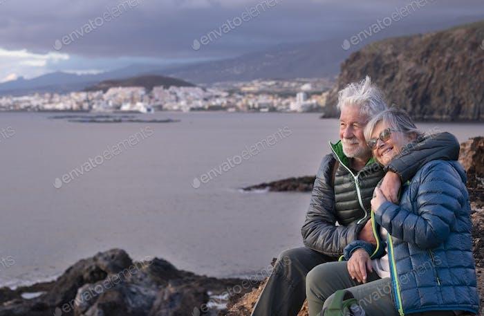 Glückliches, weißhaariges Seniorenpaar umarmt sich, das an einem Wintertag im Freien sitzt und die Freiheit genießt
